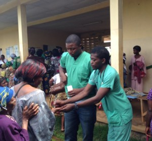 Volunteers give medication to patients
