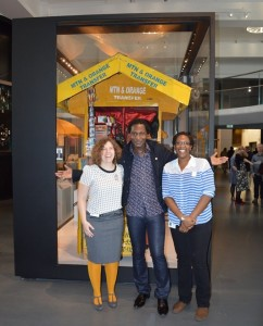 The Cameroon Call box, standing tall in the Information Age gallery. (from left to right: Charlotte Connelly, from the  Science Museum; Mbeng Pouka, famous Cameroonian painter from the Diaspora; Deanne Naula, from the Science Museum)